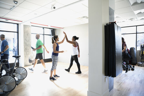 Women high-fiving after spin class in gym - HEROF11241
