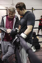 Trainer with clipboard talking to male boxer in gym - HEROF11247