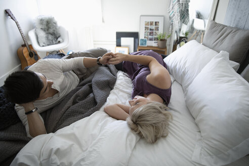Affectionate, serene couple holding hands on bed - HEROF11262