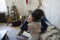 Affectionate young couple hugging in Christmas living room - HEROF11271