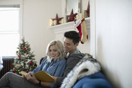 Affectionate young couple reading book in Christmas living room - HEROF11280