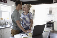 Affectionate, happy couple at laptop in kitchen - HEROF11292