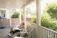 Carefree woman relaxing on summer porch - HEROF11295