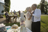 Affectionate senior bride and groom standing at wedding cake - HEROF11331