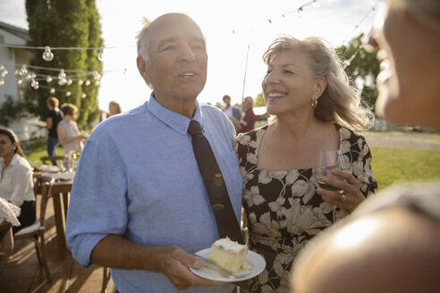 Affectionate couple eating cake and drinking wine, celebrating anniversary at sunny, rural garden party - HEROF11346