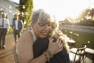 Affectionate senior bride hugging friend in sunny rural garden - HEROF11349
