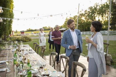 Couple drinking champagne, talking at wedding reception in rural garden - HEROF11352