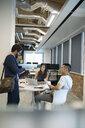 Business people using laptop, talking in open plan office - HEROF11397