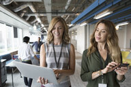 Businesswomen walking with laptop and smart phone in office - HEROF11433