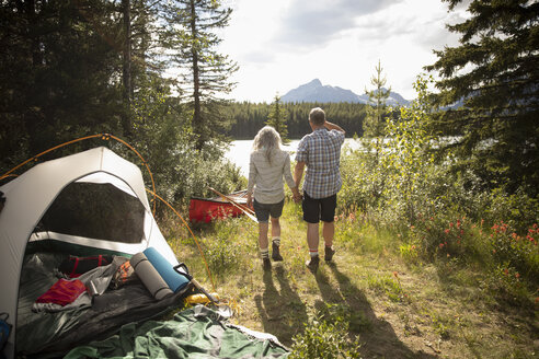 Affectionate mature couple holding hands at sunny forest campsite, Alberta, Canada - HEROF11445