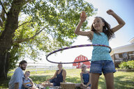 Family enjoying picnic, watching daughter playing, spinning in plastic hoop on rural farm - HEROF11556
