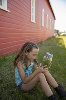Curious girl with insect jar sitting in grass along red barn on rural farm - HEROF11559