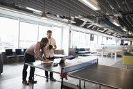 Creative businessmen using laptop on ping pong table - HEROF11580