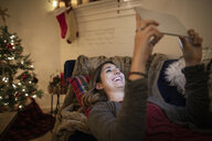 Happy young woman using digital tablet in Christmas living room - HEROF11628