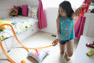 Girl playing with toy car track in bedroom - HEROF11697