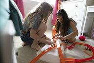 Girl friends playing with toy car track in bedroom - HEROF11703