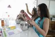 Girl friends making homemade slime in kitchen - HEROF11718