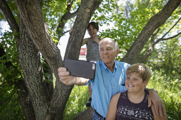 Grandfather and grandsons with smart phone taking selfie under tree - HEROF11736