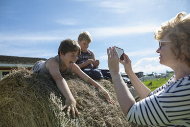 Grandmother with camera phone photographing grandsons playing on hay bale on sunny rural farm - HEROF11739