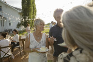 Friends celebrating, eating cake at garden party - HEROF11748