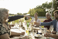 Friends drinking champagne and wine at sunny garden party patio table - HEROF11751