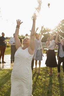 Happy senior bride throwing bouquet for cheering women in rural yard - HEROF11757