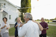 Happy senior bride and groom dancing at wedding reception in rural garden - HEROF11763