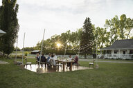 Friends eating and drinking at wedding reception table in rural garden - HEROF11766