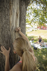 Girl carving into tree trunk on rural farm - HEROF11769