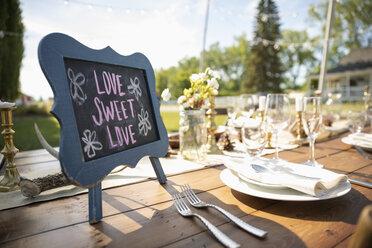Love Sweet Love blackboard sign on wedding reception patio table - HEROF11772