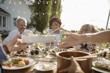 Friends eating and drinking at wedding reception at sunny rural table - HEROF11778