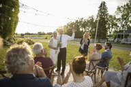 Friends clapping for senior bride and groom getting married in sunny, rural garden - HEROF11796