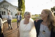Happy senior bride and friend in sunny rural garden - HEROF11799