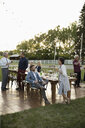Friends drinking champagne and talking at wedding reception table in rural garden - HEROF11802