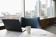 Laptop, paperwork and coffee cup on table in highrise office - HEROF11808