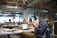 Focused businessman using laptop, listening in pizza lunch office meeting - HEROF11817