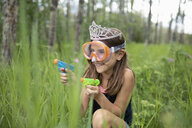 Playful girl in tiara and goggles crouching in tall grass with squirt guns - HEROF11877