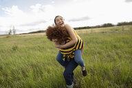Playful teenage girl friends piggybacking in rural field - HEROF11883