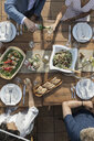 Overhead view friends enjoying lunch and wine at patio table - HEROF11889