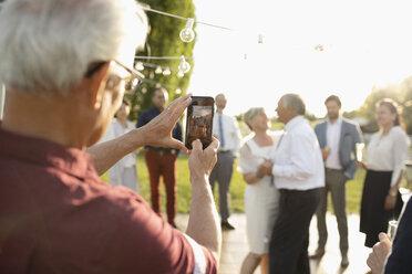 Man with camera phone photographing senior bride and groom dancing - HEROF11892