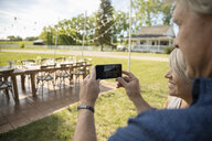 Mature couple with camera phone photographing wedding reception table in rural garden - HEROF11907