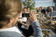 Man with camera phone photographing friends at sunny, rural garden party lunch - HEROF11910