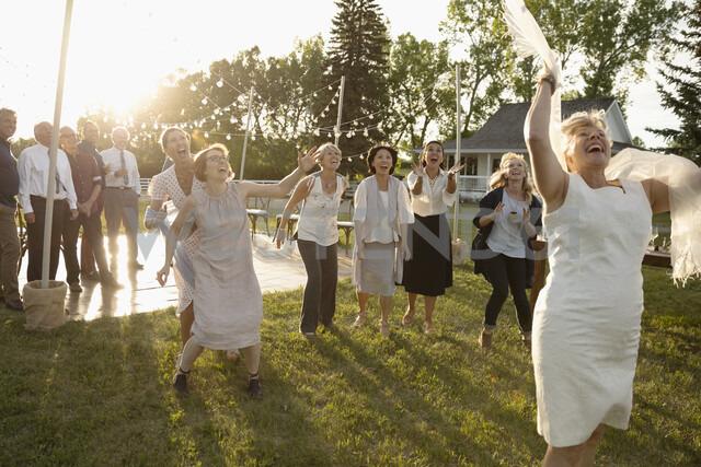 Playful senior bride throwing bouquet in sunny rural garden - HEROF11916 - Hero Images/Westend61