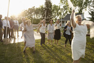Playful senior bride throwing bouquet in sunny rural garden - HEROF11916
