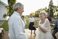 Playful senior bride and groom dancing at wedding reception in rural garden - HEROF11919