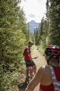 Mature couple mountain biking on sunny forest trail - HEROF11931