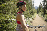 Mature woman mountain biking on sunny forest trail - HEROF11937