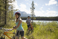 Mature couple mountain biking near sunny remote lake, Alberta, Canada - HEROF11940