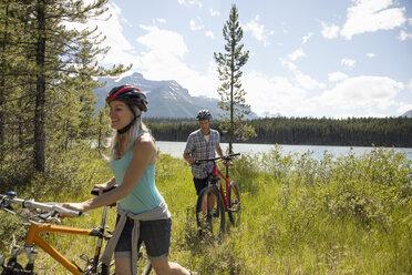 Mature couple mountain biking near sunny remote lake, Alberta, Canada - HEROF11940