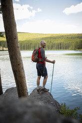 Mature man hiking with nordic walking poles, enjoying tranquil forest lake view, Alberta, Canada - HEROF11952